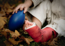 Little boy with broken leg holds football. A little boy with a broken leg in a cast holds a small football royalty free stock photo