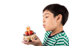 Little boy browing candle on the cake for his birthday. Celebration Stock Image