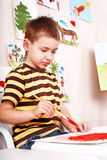 Little boy  with brush draw red sun in play room. Stock Photos