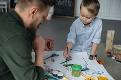 Little boy with brush and paints drawing picture together with father. At home stock photo