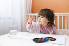 Little boy with brush and water color paints Stock Image