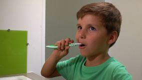 Boy cleans his teeth. Little boy brushes his teeth in the bathroom stock footage