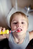 Little boy brushing teeth in bath with electric brush Royalty Free Stock Image