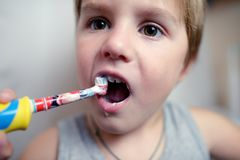 Little boy brushing teeth in bath with electric brush Stock Image