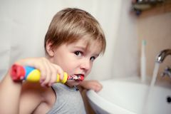 Little boy brushing teeth in bath with electric brush Royalty Free Stock Photos