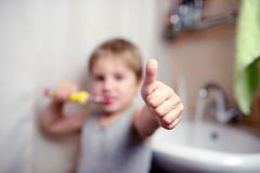 Little boy brushing teeth in bath with electric brush also shows thumbs up Royalty Free Stock Photos