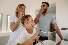 Little boy brushing teeth with his parents. In bathroom. Family brushing teeth together in bathroom Royalty Free Stock Images