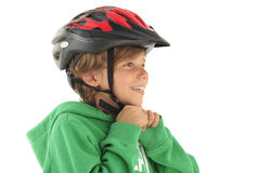 Little boy buckle up his bicyle helmet. Cheerful little boy buckle up his bicyle helmet for safety sake against white background Royalty Free Stock Photos