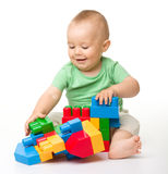 Little boy with building bricks. Cute little boy is playing with building bricks while sitting on floor, isolated over white royalty free stock photo