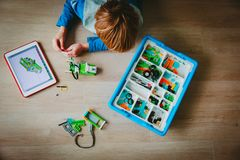 Little boy building robot and programming it with touch pad. Little boy building robot from plastic blocks and programming it with touch pad royalty free stock photos