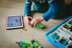 Little boy building robot and programming it with touch pad. Little boy building robot from plastic blocks and programming it with touch pad stock photo