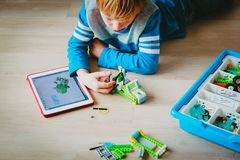 Little boy building robot and programming it with touch pad. Little boy building robot from plastic blocks and programming it with touch pad stock image