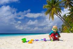 Little boy building sand castle on beach Stock Photos