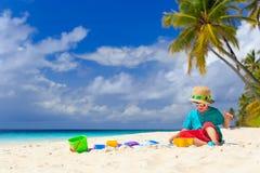 Little boy building sand castle on beach Stock Images