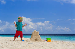 Little boy building sand castle on beach Stock Photo