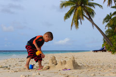 Little boy building sand castle on tropical beach Royalty Free Stock Image