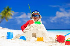 Little boy building sandcastle on beach Stock Photos