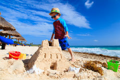 Little boy building sandcastle on sand beach Stock Photo