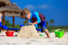 Little boy building sandcastle on summer beach Stock Photos
