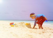 Little boy building sandcastle on tropical beach Stock Photography