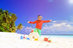 Little boy building sandcastle on tropical beach Stock Images