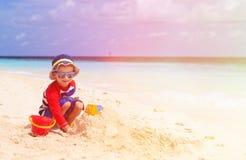Little boy building sandcastle on tropical beach Stock Photos
