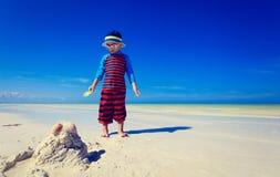 Little boy building sandcastle on tropical beach Stock Images