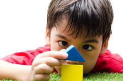 Little boy building a small house with colorful wooden blocks Stock Photos