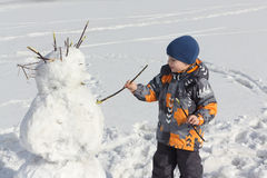 The little boy  building a snowman in the winte Royalty Free Stock Photo