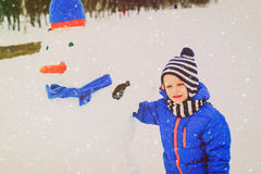 Little boy building snowman in winter nature Royalty Free Stock Image