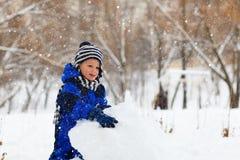 Little boy building snowman in winter park Stock Image