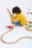 Little boy builds barrier for wooden railway Royalty Free Stock Photography