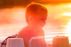 Little boy builds figures of sand on the river bank at sunset Stock Photos