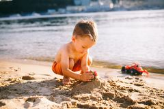 A little boy builds figures of sand on the river bank at sunset the day, hands make shapes from wet sand. A little boy builds figures of sand on the river bank Stock Image