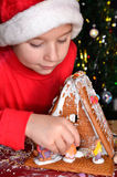 Little boy builds a house out of gingerbread Royalty Free Stock Images
