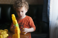 Little boy builds a tower. Two year old boy builds a tower from the constructor. Looks like his tower falls. Hes worried about it. He is curly-headed. The scene Stock Photos