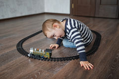 Little boy builds toy railroad Royalty Free Stock Photos