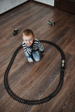 Little boy builds toy railroad Stock Photos