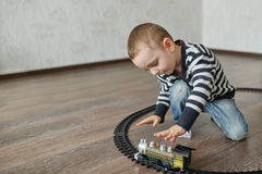 Little boy builds toy railroad Stock Photography