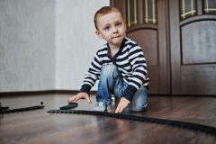 Little boy builds toy railroad Royalty Free Stock Images
