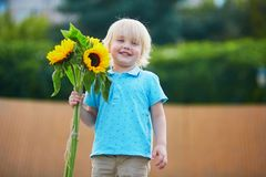Little boy with bunch of sunflowers outdoors Stock Photo