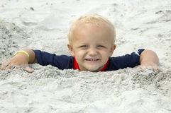 Little Boy Buried in Sand up to Head. Little Boy Smiles Buried in Beach Sand up to Head Stock Image