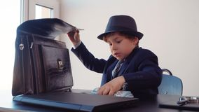 Little boy business boss at business table hiding money stack in briefcase in office. Young business boss in black suite stock video footage