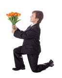 Little boy in business suit giving flowers to somebody isolated. On white background Stock Photography
