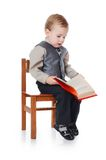The little boy in a business suit reads the book Stock Photography