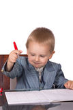 Little boy in a business suit signs documents stock image