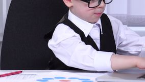 Little boy businessman looking at charts and data are entered into a laptop stock video