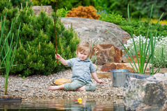 Little boy busy catching fish in the pond Stock Photos