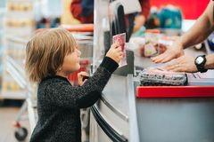 Little boy buying fruits in a food store stock photo