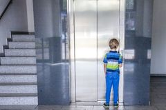 Little boy is calling the elevator Royalty Free Stock Image